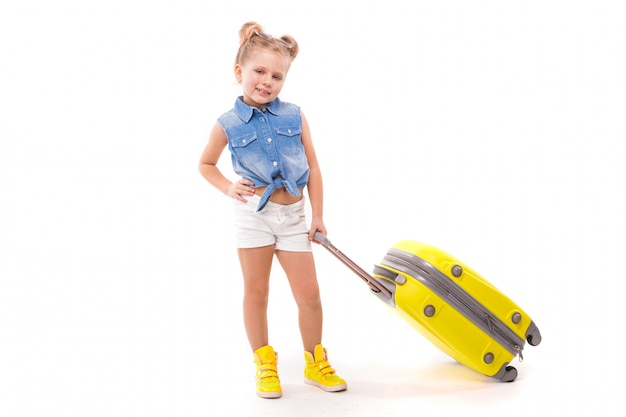 c9fd94e44eab Pretty little girl in blue shirt, white shorts and sunglasses hold yellow  suitcase by the