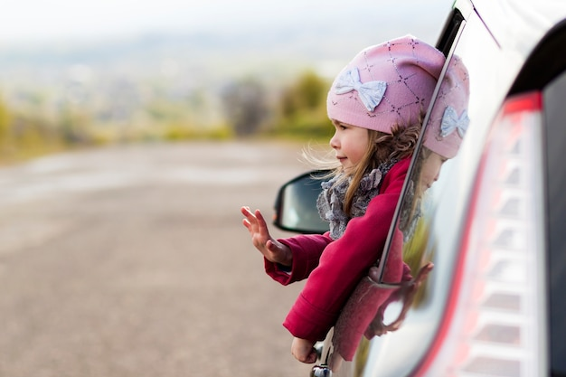 Pretty little girl in the car looking through car window. Premium Photo