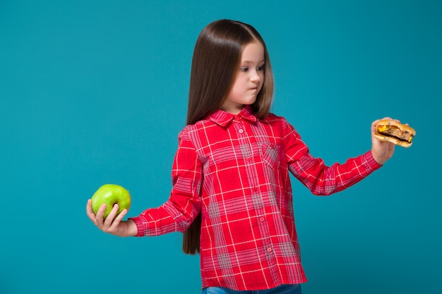Pretty, little girl in checkered shirt with brunet hair hold burger Premium Photo