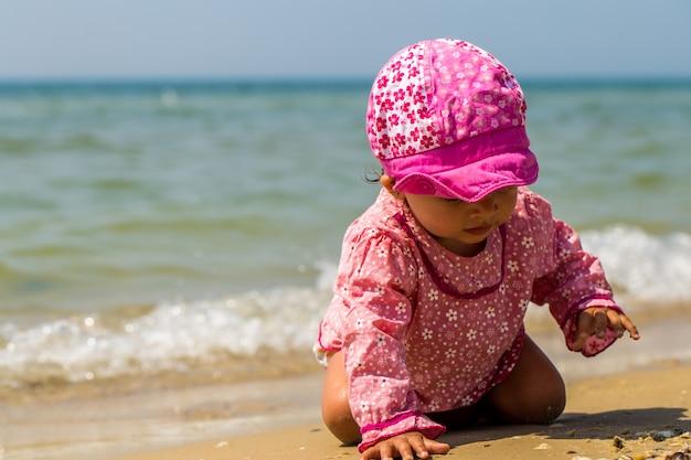 Pretty little girl crawling on the beach, the joyful child, emotions Free Photo