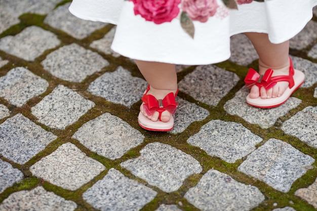 Хорошенькая девочка 1 года делает первый шаг. симпатичные ножки маленького ребенка в красных сандалиях на улице крупным планом Premium Фотографии