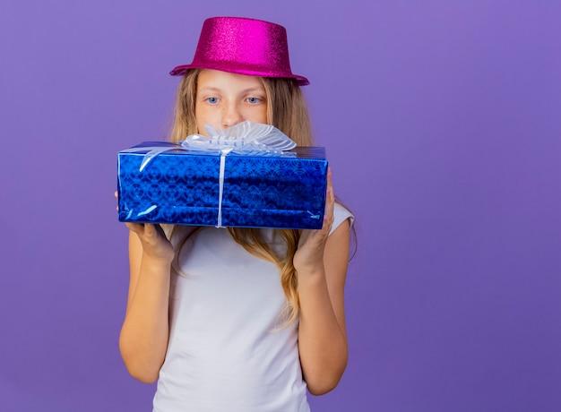 선물 상자를 들고 휴가 모자에 예쁜 소녀, 보라색 배경 위에 서있는 생일 파티 개념 호기심을 찾고 무료 사진