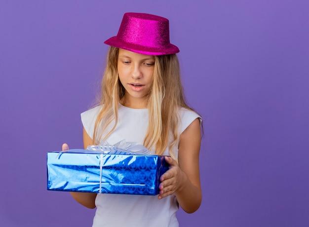驚き、紫色の背景の上に立っている誕生日パーティーのコンセプトを見てギフトボックスを保持している休日の帽子のかわいい女の子 無料写真