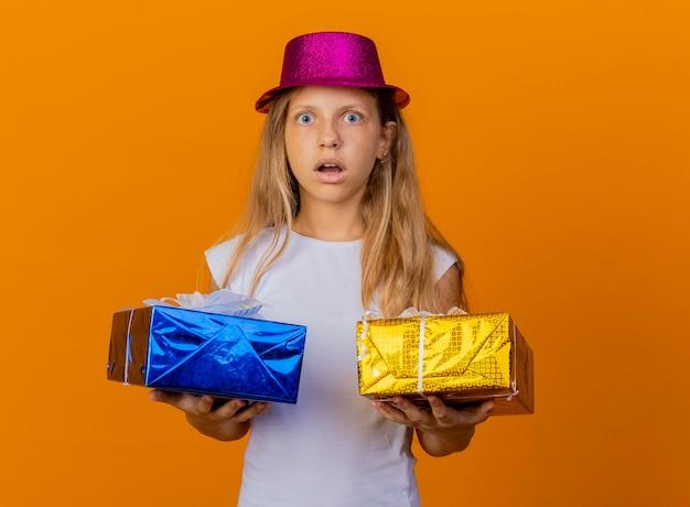 카메라를보고 선물 상자를 들고 휴가 모자에 예쁜 소녀 놀라게하고 놀란, 오렌지 배경 위에 생일 파티 개념 서 무료 사진