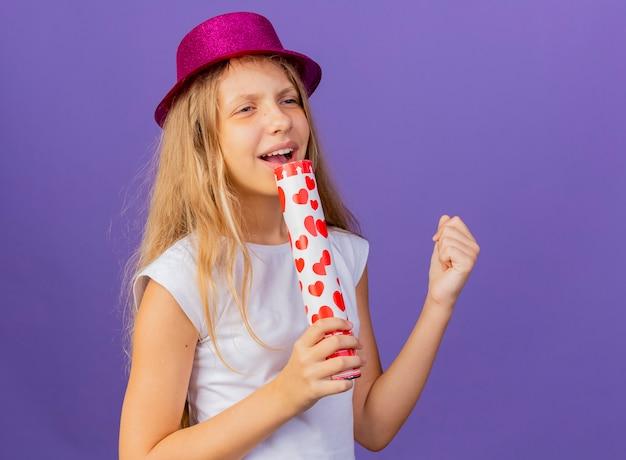 마이크 노래로 사용하는 파티 크래커를 들고 휴가 모자에 예쁜 소녀, 보라색 배경 위에 서있는 생일 파티 개념 무료 사진