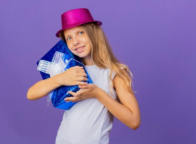행복 한 얼굴 미소, 보라색 배경 위에 서있는 생일 파티 개념으로 카메라를 찾고 휴가 모자 포옹 선물 상자에 예쁜 소녀 무료 사진