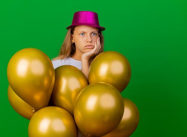 옆으로 의아해 보이는 Baloons의 무리와 함께 휴가 모자에 예쁜 소녀, 녹색 배경 위에 서 생일 파티 개념 무료 사진