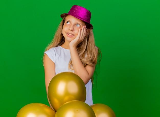 緑の背景の上に立っている誕生日パーティーのコンセプト、笑顔と思考を脇に見て風船の束と休日の帽子のかわいい女の子 無料写真