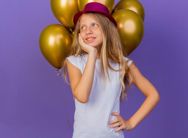 紫色の背景の上に立っている幸せな顔の笑顔、誕生日パーティーのコンセプトを感じて脇を見て風船の束と休日の帽子のかわいい女の子 無料写真