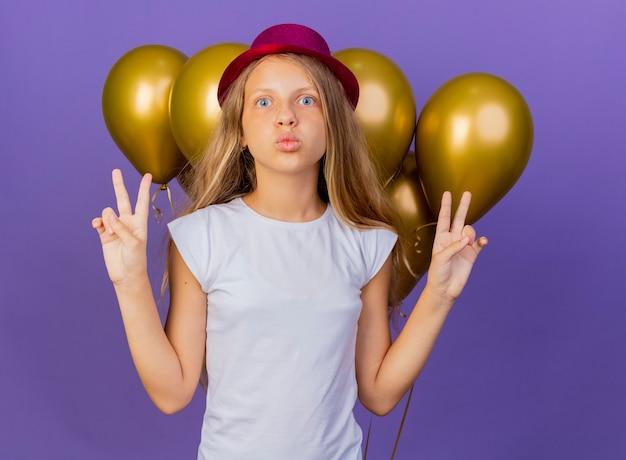 紫色の背景の上に立っているvサイン、誕生日パーティーのコンセプトを示す幸せでポジティブなカメラを見て風船の束と休日の帽子のかわいい女の子 無料写真