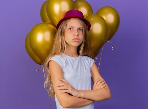 심각한 얼굴로 카메라를 찾고 Baloons의 무리와 함께 휴가 모자에 예쁜 소녀, 보라색 배경 위에 서있는 생일 파티 개념 무료 사진