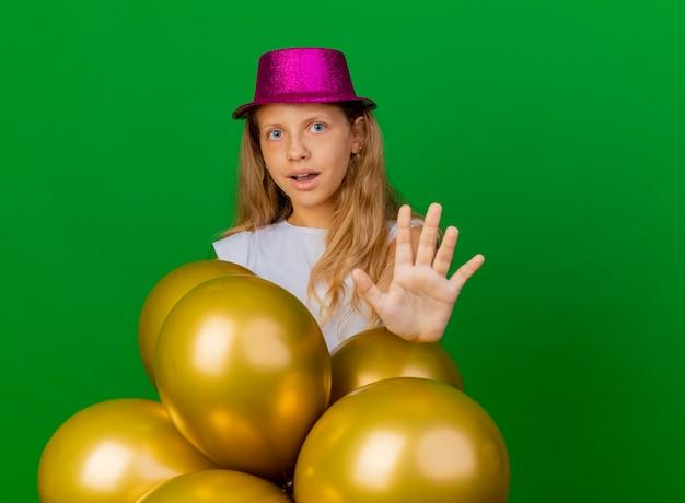 手で一時停止の標識を作る風船の束、緑の背景の上に立っている誕生日パーティーのコンセプトを持つ休日の帽子のかわいい女の子 無料写真