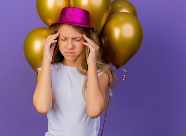 頭痛、紫色の背景の上に立っている誕生日パーティーのコンセプトを持つ彼女の寺院に触れる風船の束と休日の帽子のかわいい女の子 無料写真