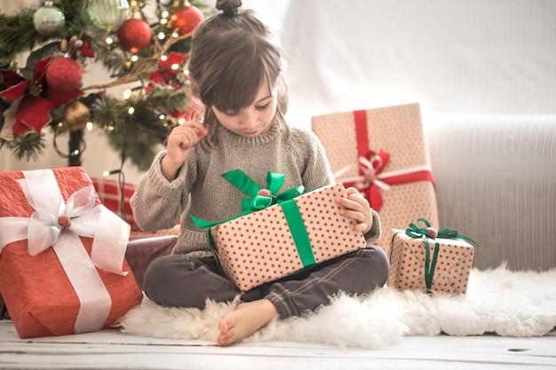 집에서 그녀의 방에 그녀의 침대에 앉아있는 동안 예쁜 소녀는 선물 상자를 들고 웃 무료 사진