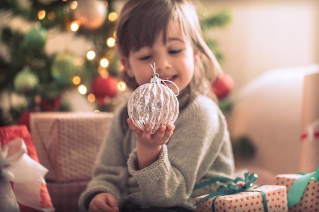 예쁜 소녀는 선물 상자를 들고 집에서 그녀의 방에있는 그녀의 침대에 앉아있는 동안 웃고 있습니다. 무료 사진