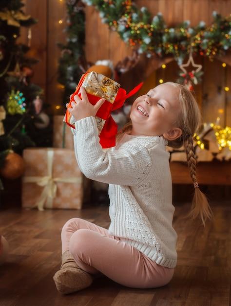 Pretty little girl opens a christmas present. Premium Photo