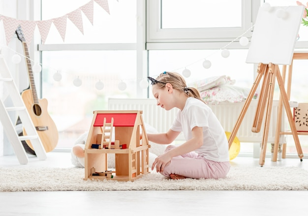 Premium Photo Pretty Little Girl Playing With Dollhouse