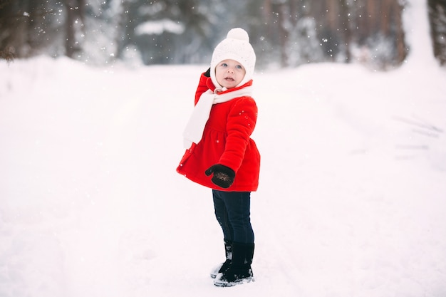 Pretty little girl in red coat in winter forest. little girl having fun on winter day. cheerful little baby girl in gloves and white hat runs on snow white Premium Photo