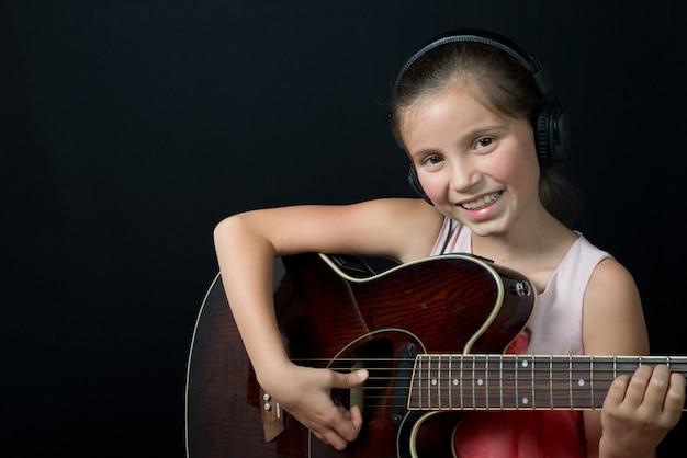 A pretty little girl whit headphones playing guitar Premium Photo
