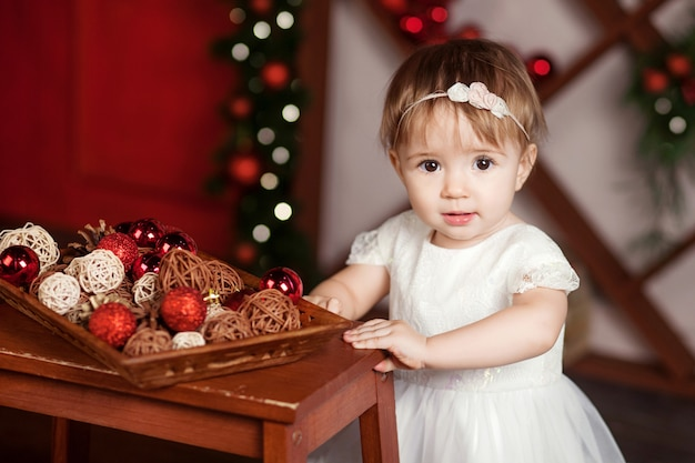 Pretty little girl in white dress playing and being happy about christmas and lights Premium Photo