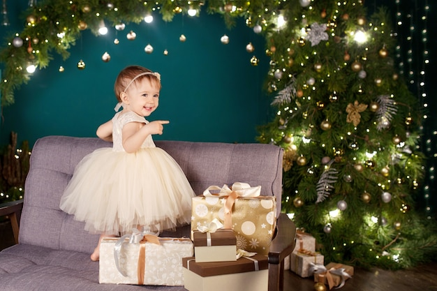 Pretty little girl in white dress playing and being happy about christmas  lights Premium Photo