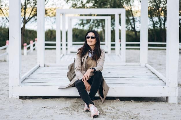 Pretty long hair brunette girl in sunglasses relaxing outdoor. Premium Photo