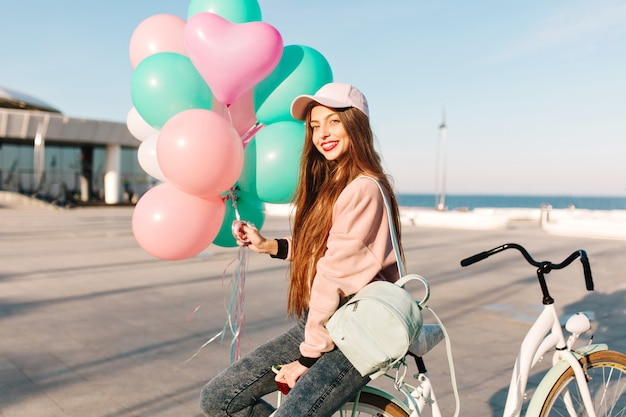 Pretty long-haired girl in pink outfit sitting on the bicycle with balloons waiting for friend from voyage. Free Photo