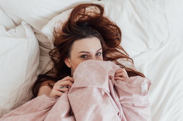 La giovane donna abbastanza adorabile fa capolino dalle coperte delle lenzuola Foto Gratuite