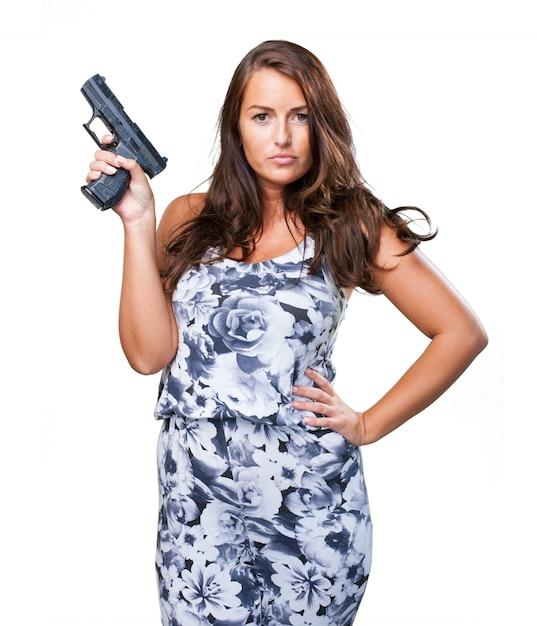 Pretty mafia woman holding a gun Free Photo