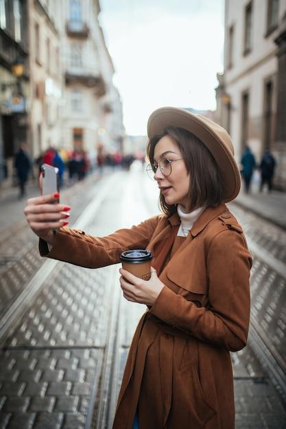かなりのモデルが街で彼女の携帯電話を保持しながらselfieを取る 無料写真