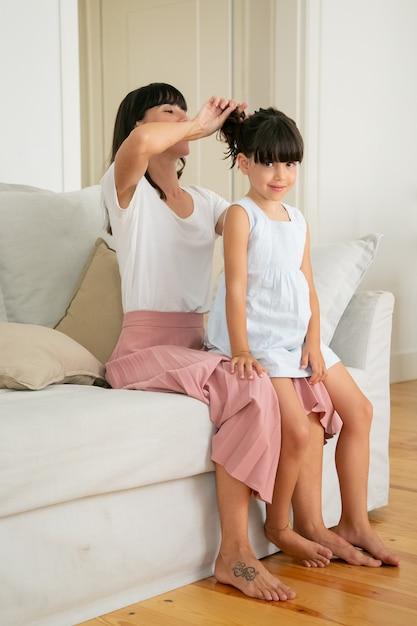 ソファの上に座って、かわいい女の子の髪型をやっているかなりママ。 無料写真