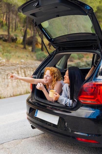 Pretty multiethnic girlfriends in open machine trunk Free Photo