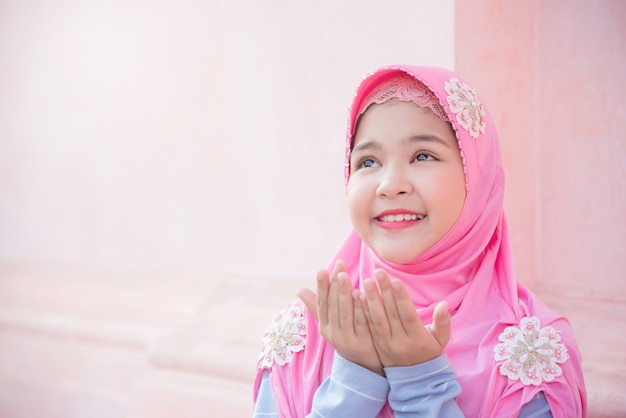 Pretty muslim girl is raising hands ask for blessing from god. Premium Photo