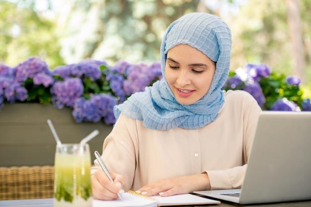 Довольно мусульманский студент в хиджабе, делая заметки в блокноте, сидя перед ноутбуком, работая над проектом на открытом воздухе Premium Фотографии