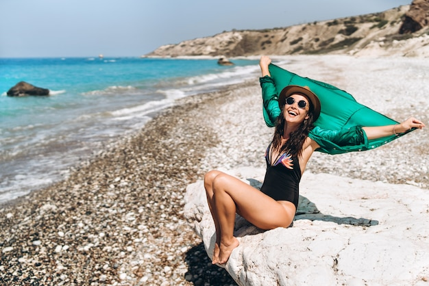 Pretty pan asian travel girl relaxing on the beach at the sea in green pareo. Premium Photo