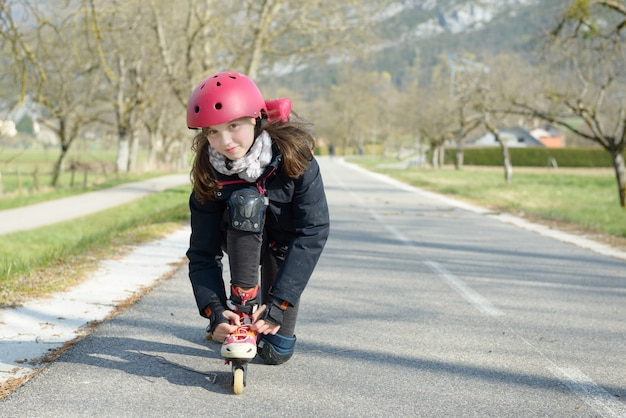 Pretty preteen girl on roller skates in helmet at a track Premium Photo