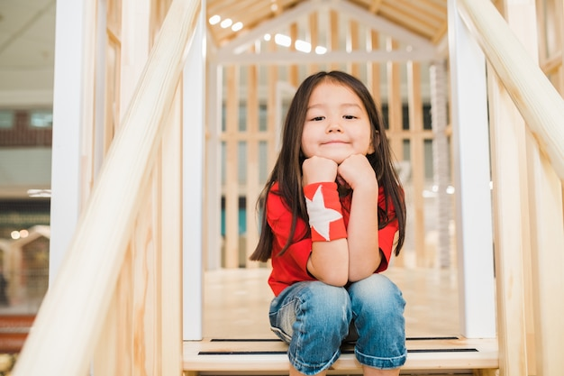 Pretty restful little girl in blue jeans and red t-shirt sitting on wooden stairs at play area between railings Premium Photo