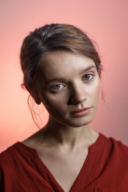Pretty sensual caucasian girl in red shirt looking into camera and tilting her head. beauty portrait on pink background Premium Photo