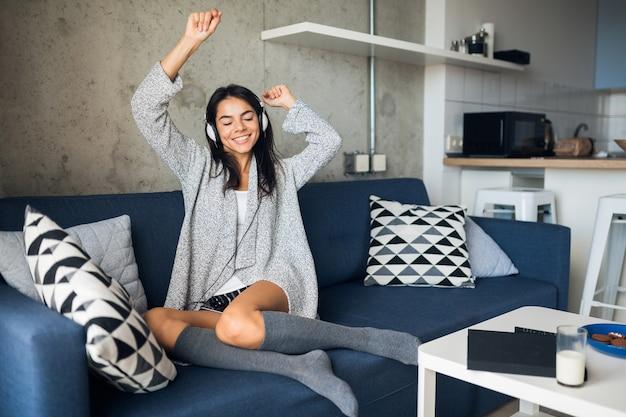 Donna sorridente abbastanza sexy in abito casual seduto in salotto ascoltando musica in cuffia, divertendosi a casa Foto Gratuite