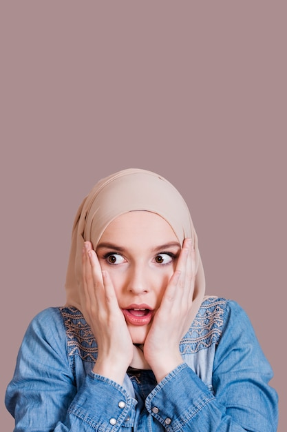 Pretty shocked muslim woman with covered head over studio background Free Photo