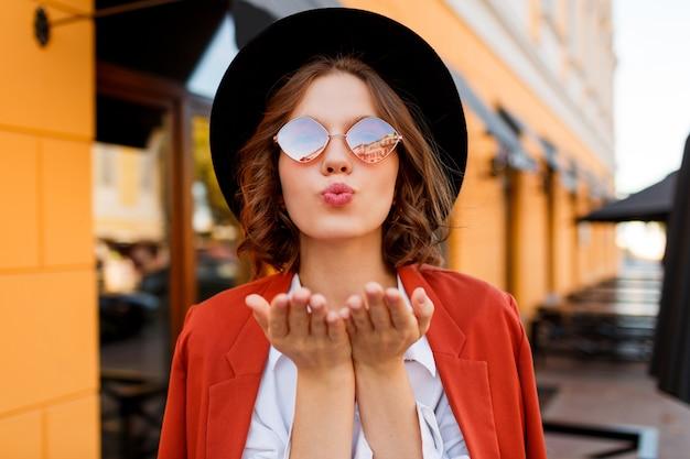 Довольно короткошерстная женщина посылает воздушный поцелуй. стильный осенний образ. Бесплатные Фотографии