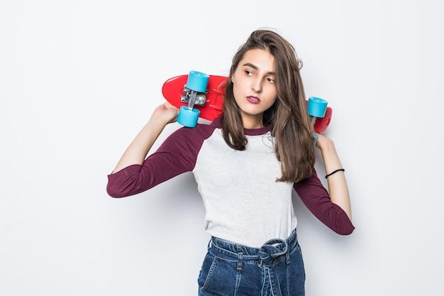 白い壁に隔離された彼女の背中に赤いスケートボードを保持しているかわいいスケーターの女の子 無料写真