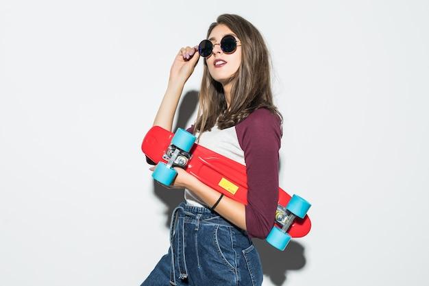 Симпатичная фигуристка в повседневной одежде и солнцезащитных очках держит красный скейтборд Бесплатные Фотографии