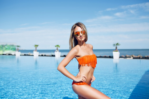 Pretty slim blond girl is standing near pool on the sun.  she is posing and smiling to the camera. Free Photo