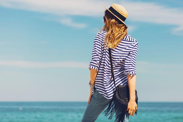 Довольно стройная загорелая стильная блондинка в соломенной шляпе и солнцезащитных очках позирует на райском тропическом пляже Бесплатные Фотографии