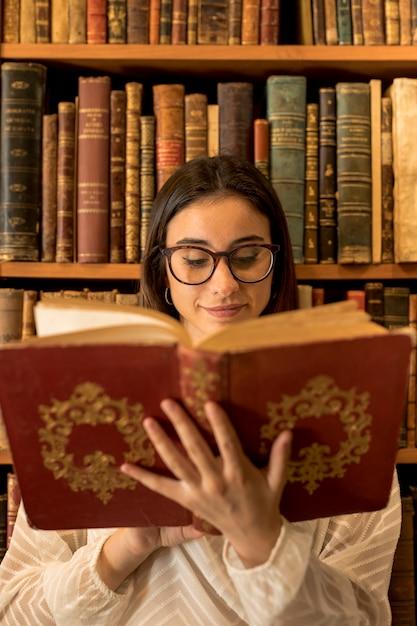 Pretty smart woman reading book near shelf Free Photo