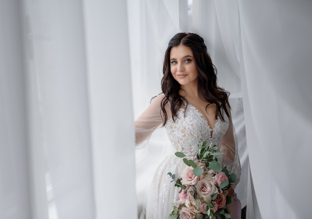 Pretty smiled brunette bride is holding tender wedding bouquet near the window and looking straight Free Photo