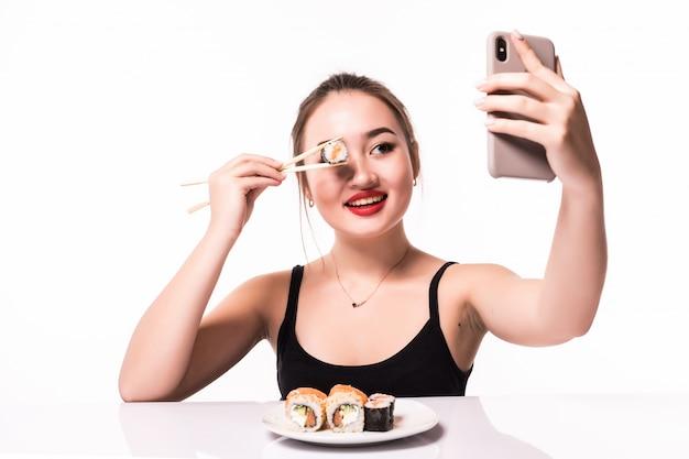 かなり笑顔のアジアの女性は巻き寿司で彼女の目を覆い、彼女の電話でselfieを作る 無料写真