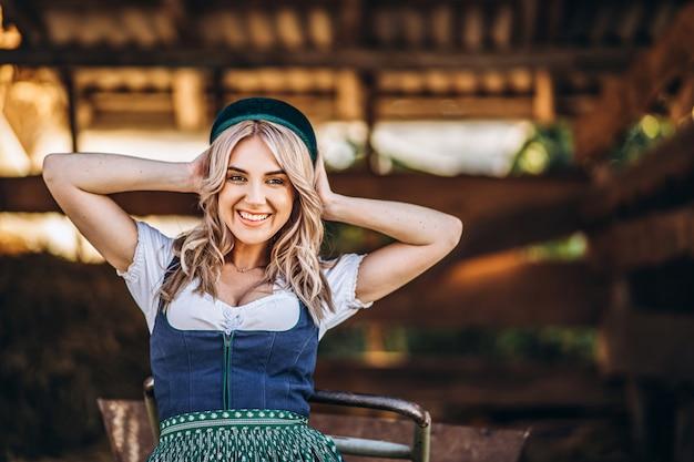 裏庭で働く手押し車で伝統的な衣装でかなり笑顔のブロンド。 Premium写真