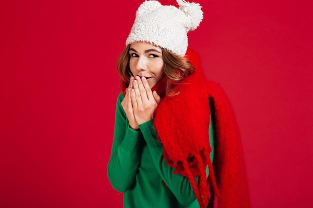 Donna castana abbastanza sorridente in maglione, cappello divertente e sciarpa Foto Gratuite